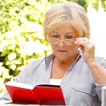 Female patient sitting outside on patio holding up eyeglasses while reading a book.